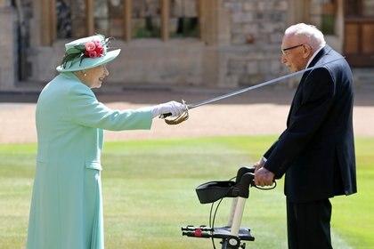 En el medio de la pandemia, en los jardínes del Castillo de Windsor, la Reina Isabel II nombró 'Sir' a Tom Moore. El título es concedido por la monarca colocando una espada en los hombros de la persona homenajeada.