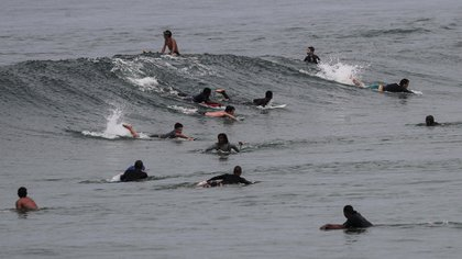 Surfistas practican en la playa de Leme, en Río de Janeiro (EFE/Antonio Lacerda)