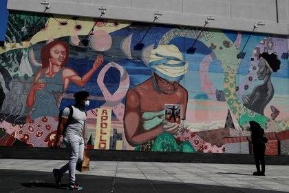 Un hombre con mascarilla pasa por un mural en el barrio de Harlem de la ciudad de Nueva York, Nueva York, EEUU, el 9 de julio de 2020. REUTERS/Shannon Stapleton