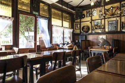 El interior del café está decorado con botellas y portaretratos de personalidades de la música y sobre todo del tango