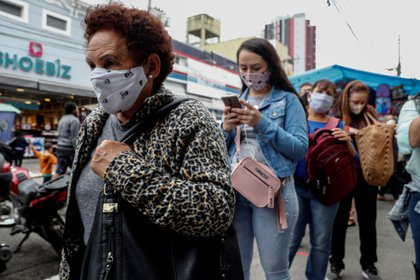 Personas con tapabocas hacen fila en un sector comercial de Sao Paulo (Brasil). EFE/ Sebastiao Moreira/Archivo