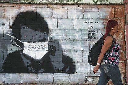 Una mujer camina delante de un graffity que burla al presidente, Jair Bolsonaro en Río de Janeiro (REUTERS/Sergio Moraes)