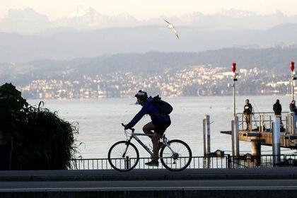 Un hombre va en bicicleta a lo largo de las orillas del Lago de Zurich, el 6 de agosto de 2020 (REUTERS/Arnd Wiegmann)
