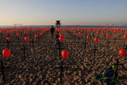 Una persona entre las cruces y globos colocados por miembros de la ONG Río de Paz en homenaje a las cien mil víctimas fatales de COVID-19 en el país, en la playa de Copacabana en Río de Janeiro (Reuters)