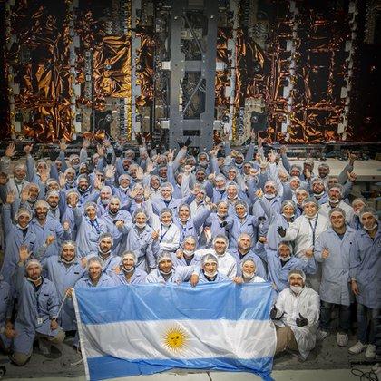Los ingenieros argentinos posan orgulloso con el satélite ya construido (Conae)