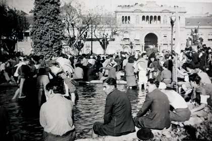 Al atardecer, la multitud ya completaba la Plaza de Mayo. Hacía calor. Muchos de ellos, que llegaban al centro porteño por primera vez en sus vidas, refrescaron sus pies en el agua de la fuente (AGN)