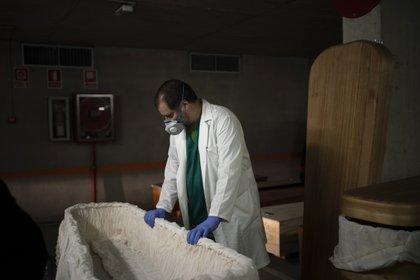 En esta foto de archivo del 14 de abril de 2020, el jefe de la funeraria Jordi Fernández prepara un ataúd antes de colocar el cuerpo de una víctima del COVID-19 en un estacionamiento subterráneo convertido en una morgue en la funeraria Collserola en Barcelona. (Foto AP / Felipe Dana, Archivo)
