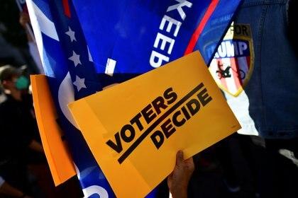 """Un letrero de """"Los Votantes Deciden"""" se muestra en una manifestación afuera del Centro de Convenciones de Filadelfia, donde se seguían contando los votos, dos días después de las elecciones presidenciales de EEUU, el 5 de noviembre de 2020.  REUTERS/Mark Makela"""