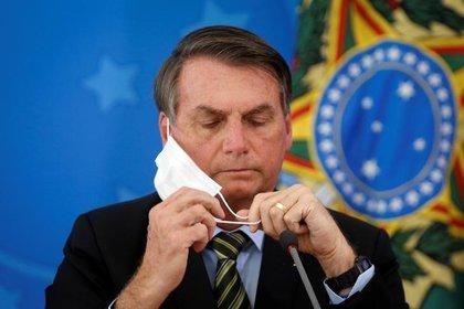 Imagen de archivo del presidente de Brasil, Jair Bolsonaro, ajustando su mascarilla durante una conferencia de prensa para anunciar medidas sobre el coronavirus, en Brasilia, Marzo 18, 2020. REUTERS/Adriano Machado