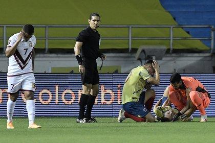 Santiago Arias (abajo) de Colombia recibe atención tras caer lesionado en un partido de las Eliminatorias Sudamericanas para el Mundial Catar 2022). EFE/Gabriel Aponte /Archivo