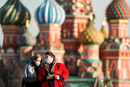 Women with protective masks, widely used as a preventive measure against coronavirus disease (COVID-19), walk across Red Square near the St. Basil's Cathedral in central Moscow, Russia March 26, 2020. REUTERS/Shamil Zhumatov
