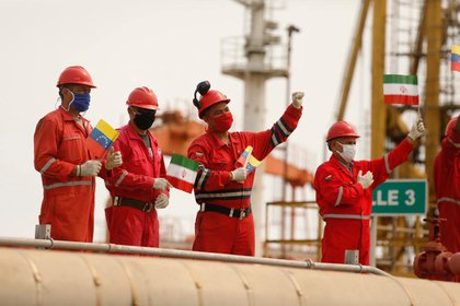 "Employees of the state oil company PDVSA with Iranian and Venezuelan flags greet each other upon the arrival of the Iranian tanker ""Wealth"" to the El Palito refinery in Porto Cabello, Venezuela.  Miraflores Palace / Material ATTENTION TO ROTERS.  Archive"