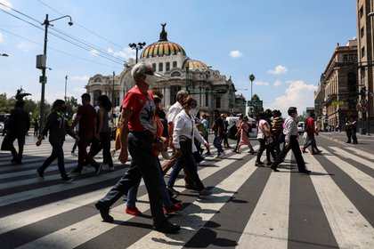 People cross a road near Zocalo Square during the gradual reopening of commercial activities in the city, as the coronavirus disease (COVID-19) outbreak continues, in Mexico City, Mexico July 13, 2020. REUTERS/Henry Romero