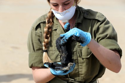 Una soldado israelí trabaja en la descontaminación de una playa (REUTERS / Ronen Zvulun)