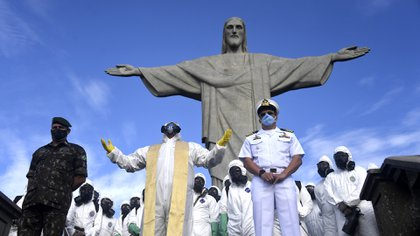 Corcovado Sanctuary's Father Omar Raposo (C) prays among members of the Brazilian Armed Forces during the disinfection of the Christ The Redeemer statue at the Corcovado mountain prior to the opening of the touristic attraction on August 15, in Rio de Janeiro, Brazil, on August 13, 2020, amid the COVID-19 novel coronavirus pandemic. (Photo by Mauro PIMENTEL / AFP)