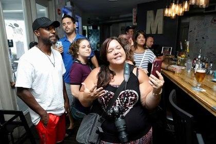 """Tara Hill (al centro) protesta con Carrie Hudson, la dueña del restaurante 33 & Melt, durante una cena """"sin máscara"""" en el restaurante para protestar por las restricciones obligatorias durante la pandemia de la enfermedad del coronavirus (COVID-19) en Windermere, Florida, Estados Unidos. 11 de julio de 2020.  REUTERS/Octavio Jones"""