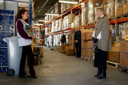 Máxima visitando la Cruz Roja respetando la distancia social luciendo una capa cuadrillé y guantes negros (AFP)