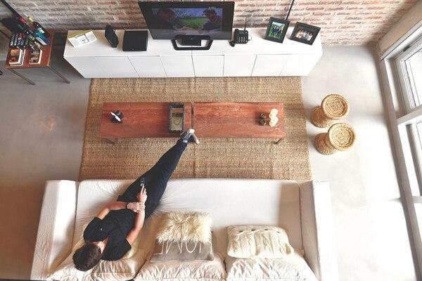El living visto desde arriba. Frente al cómodo sofá con funda de gabardina se ubica el mueble de tevé, de madera laqueada. Una mesita de hierro auxiliar brinda un plano de apoyo extra. Foto Gustavo Bosco/ Para Ti