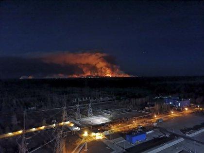En esta imagen tomada desde la azotea de la central nuclear de Chernobyl, en Ucrania, el viernes 10 de abril de 2020, se ve un incendio forestal cerca de la planta en la zona de exclusión. (Oficina de Prensa de la Policía de Ucrania via AP)