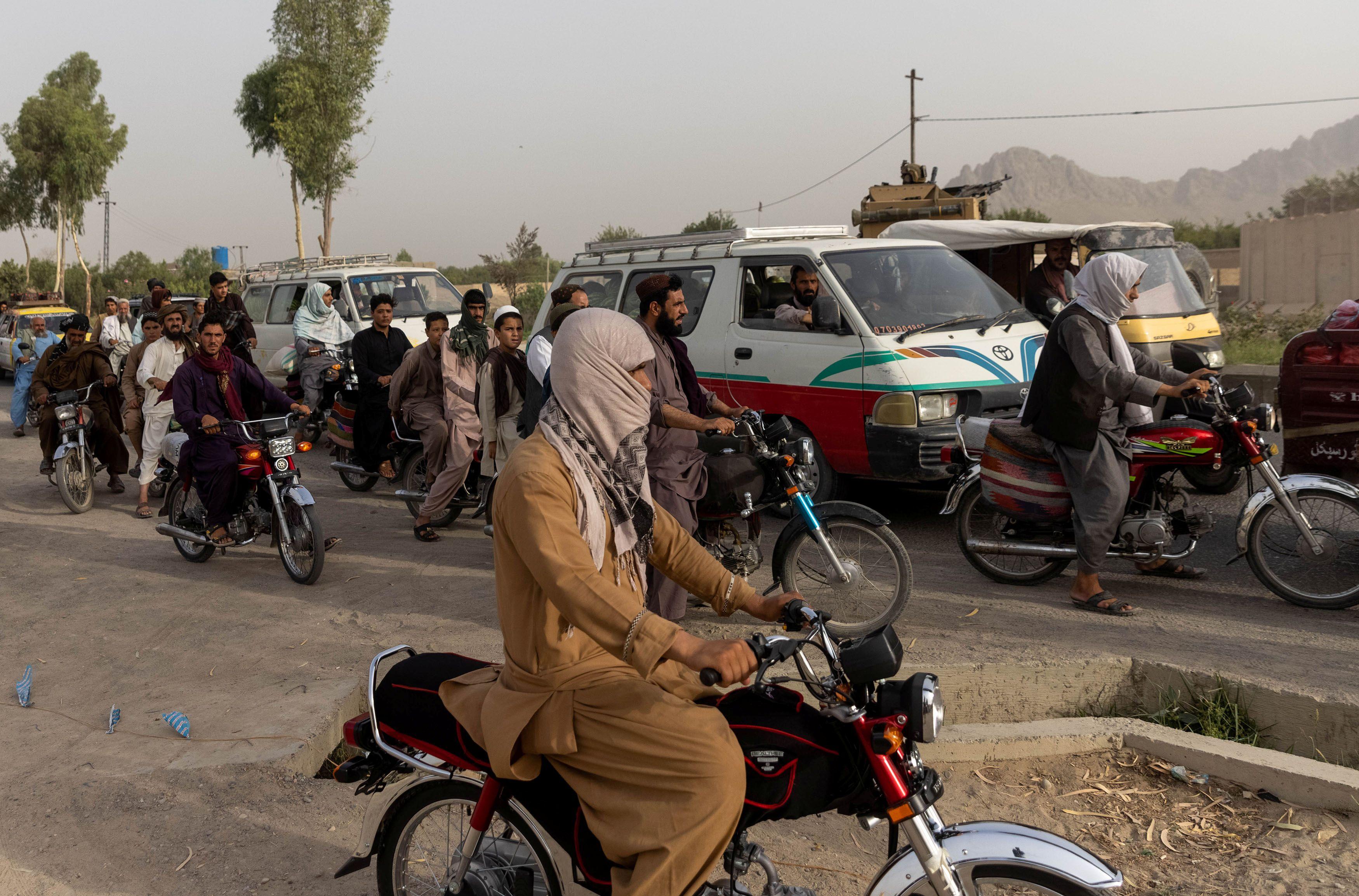 El tráfico se detiene mientras miembros de las fuerzas especiales afganas se reagrupan tras fuertes enfrentamientos con los talibanes durante la misión de rescate de un policía asediado en un puesto de control, en la provincia de Kandahar, Afganistán, el 13 de julio de 2021.