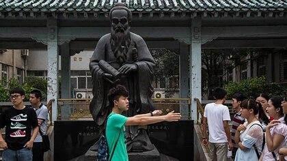 Estudiantes reunidos frente a una escultura de Confucio en la Universidad de Wuhan, en la provincia de Hubei