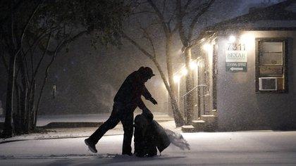 Dos personas juegan en la nieve en San Antonio, Texas, una de las ciudades afectadas por los cortes de energia eléctrica