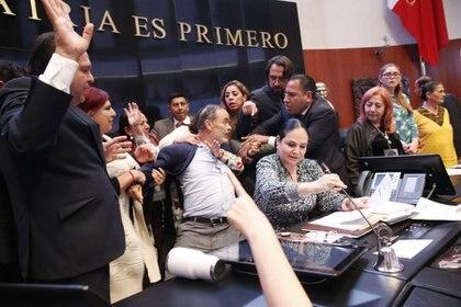 En medio de las protestas ocurridas durante la toma de protesta Rosario Piedra Ibarra, como nueva titular de la Comisión Nacional de Derechos Humanos, Gustavo Madero, senador del PAN cayó en plena tribuna de la cámara alta. FOTO: CUARTOSCURO