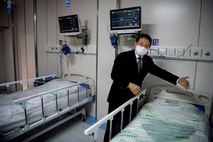 El doctor Lu Hongzhou, codirector del Centro Clínico Público de Shanghai, muestra una sala de cuarentena para pacientes con coronavirus en el edificio A2 en Shanghai, China, el 17 de febrero de 2020 (Noel Celis/Pool via REUTERS)