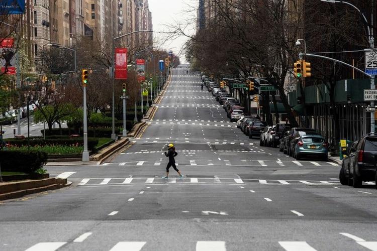Imagen de archivo de una mujer cruzando una calle vacía de Park Avenue en Manhattan, en medio de la propagación de la enfermedad provocada por el coronavirus, COVID-19, en Nueva York (Reuters)