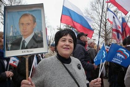 Una mujer que sostiene un retrato del presidente ruso Vladimir Putin participa en una manifestación que conmemora el tercer aniversario de la votación de Crimea para abandonar Ucrania y unirse al estado ruso en el centro de Simferopol el 16 de marzo de 2017. / AFP PHOTO / Max Vetrov