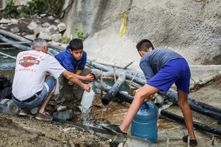 Un grupo de personas toma agua de una tubería de una construcción abandonada en la Avenida Baralt, en el centro de Caracas (Venezuela). La falta de agua causada por una semana de apagones en Venezuela terminó empujando a los venezolanos a las calles (EFE)