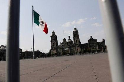 La bandera mexicana en la plaza cerrada del Zócalo, después de que el gobierno mexicano declaró una emergencia de salud y emitió regulaciones más estrictas para contener la propagación de la enfermedad por coronavirus (COVID-19), en Ciudad de México. 13 de abril de 2020. REUTERS/Henry Romero