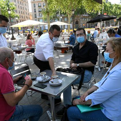People wearing masks sit at a terrace bar at in Las Ramblas in Barcelona on May 25, 2020. - Coronavirus lockdown measures will finally be eased for people in Madrid and Barcelona, while elsewhere in Spain the first beaches are due to reopen. Residents in the two cities can now meet in groups of up to 10 people in their homes or on the terraces of bars and restaurants. (Photo by LLUIS GENE / AFP)