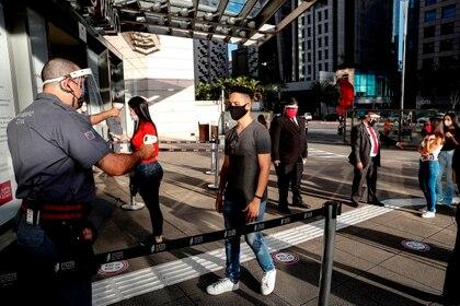 Un funcionario mide la temperatura de los clientes que ingresan a un centro comercial este jueves, en Sao Paulo (Brasil). EFE/Sebastiao Moreira