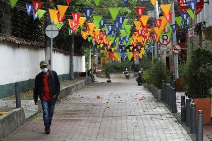 Foto de archivo. Un hombre usando tapabocas camina por una calle en uno de los barrios en donde se decretó cuarentena para contener la segunda ola de COVID-19 en Bogotá, Colombia. REUTERS/Luisa González