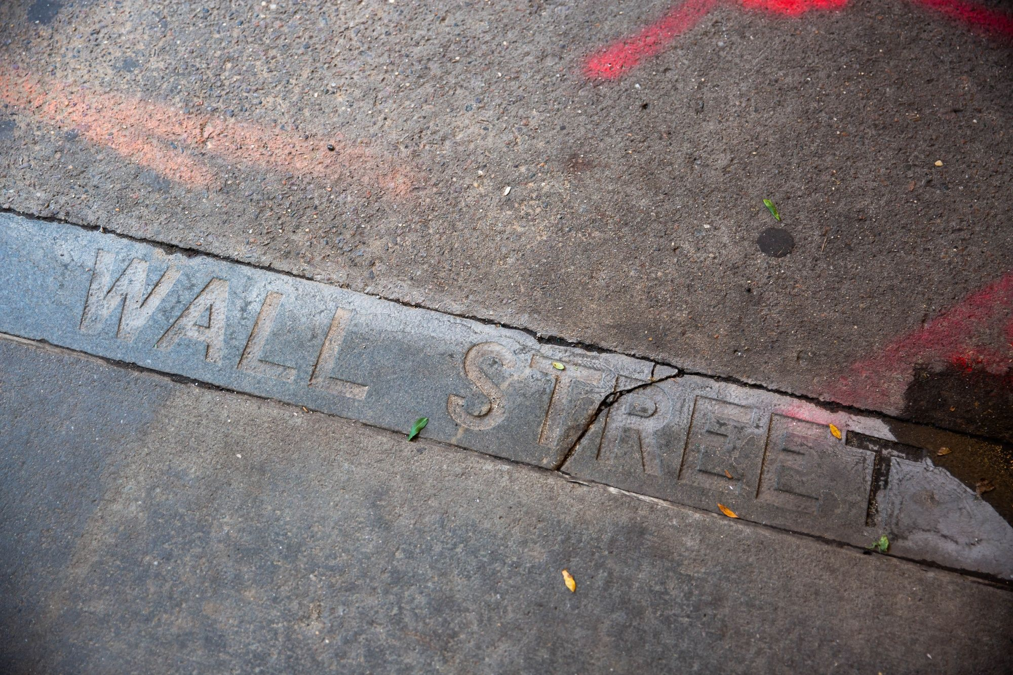 """""""Wall Street"""" etched on the curb near the New York Stock Exchange (NYSE) in New York, U.S., on Wednesday, Sept. 30, 2020. Shares of Palantir Technologies, a data mining company co-founded by technology billionaire Peter Thiel, opened trading today on the New York Stock Exchange at $10 after the company sold shares to investors in a direct offering. Photographer: Michael Nagle/Bloomberg"""