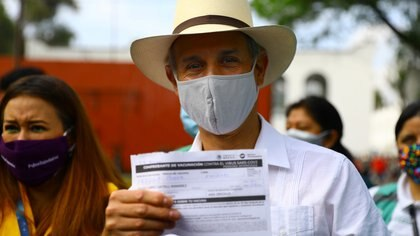 Deputy Health Minister Hugo Lopez Gatell shows a document after receiving a dose of the Pfizer/BioNTech COVID-19 vaccine in Mexico City