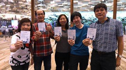 Pasajeros del vuelo inaugural de Singapore Airlines a Nueva York pose con tarjetas de recuerdo después de su check-in en el aeropuerto internacional de Changi (Photo by ROSLAN RAHMAN / AFP)