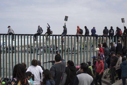 Sobre la playa, migrantes treparon a las barreras que separan Tijuana de San Diego (AP /Hans-Maximo Musielik)