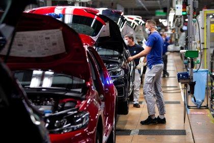 Un trabajador usa una máscara protectora en la línea de la fábrica de automóviles más grande de Europa, el 27 de abril de 2020 (Swen Pfoertner/Pool vía REUTERS/Archivo Foto)