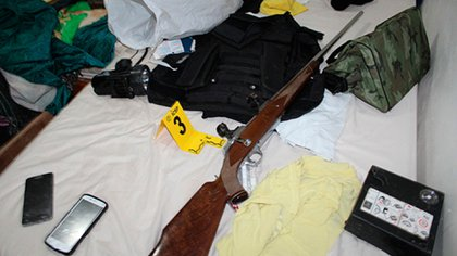 Sobre la cama, las autoriddades encontraron un chaleco antibalas, armas y municiones