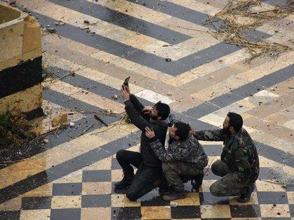 Miembros del Ejército del régimen se toman una selfie en las ruinas de una antigua mezquita