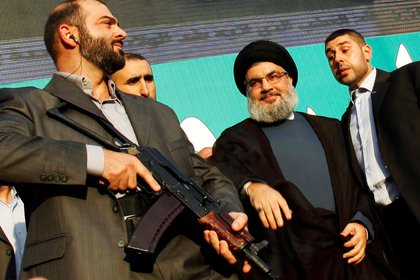 FILE PHOTO: Lebanon's Hezbollah leader Sayyed Hassan Nasrallah (2nd R), escorted by his bodyguards, greets his supporters at an anti-U.S. protest in Beirut's southern suburbs, Lebanon September 17, 2012. REUTERS/Sharif Karim/File Photo