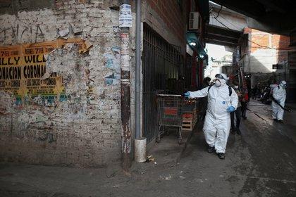 Tareas de limpieza y desinfección de la Ciudad en el barrio 31. (REUTERS/Agustin Marcarian)