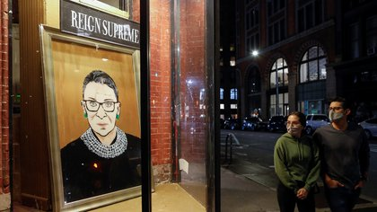 People look toward a painting in a storefront on Broadway of Associate Justice of the Supreme Court of the United States Ruth Bader Ginsburg who passed away in Manhattan, New York City, U.S., September 18, 2020. REUTERS/Andrew Kelly