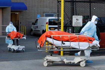 Trabajadores sanitarios de Nueva York transportan cuerpos de víctimas fatales de coronavirus. El estado es el la zona roja de la pandemia en los EEUU. (Reuters)