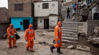 Los trabajadores de la funeraria Piedrangel Alexander Carballo (izquierda) y Luis Brito (derecha). ambos venezolanos, y el peruano Martín Águila, llegan al vecindario de El Augustino para retirar el cuerpo de un residente que se sospecha que murió por coronavirus, en Lima, Perú, el 4 de mayo de 2020. La labor de recopilar los cadáveres de supuestas víctimas del virus ha recaído en los trabajadores de la funeraria Piedrangel, que llegan a hacerse cargo de hasta 10 cuerpos al día. (AP Foto/Rodrigo Abd)