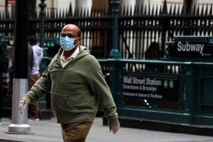 Un hombre con mascarilla y guantes camina cerca a la estación Wall Street en Nueva York (Reuters)