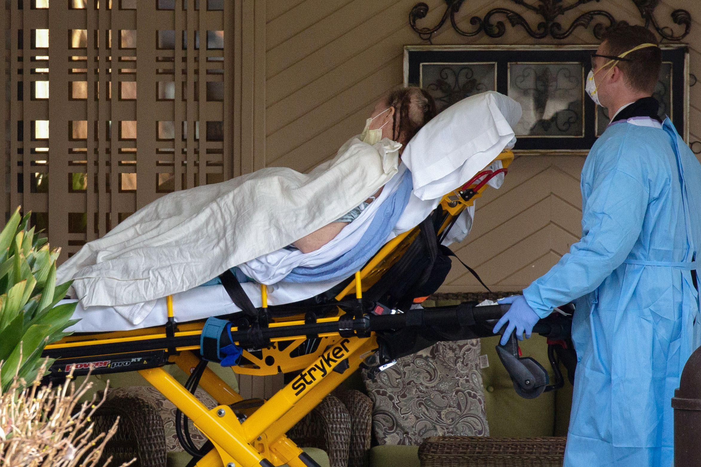 Médicos transportan a un paciente desde una ambulancia al Life Care Center de Kirkland, el centro de atención a largo plazo vinculado a casos confirmados de coronavirus en el estado, durante el brote de la enfermedad por coronavirus (COVID-19), en Kirkland, Washington (Reuters)