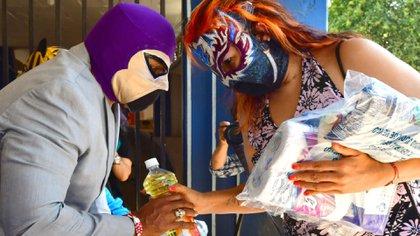 """El presidente de la Asociación de Lucha Libre de México, """"El Fantasma"""", entrega alimentos a la luchadora activa, La Zorrita (Foto: EFE)"""